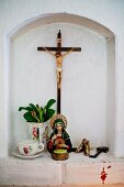 Devotional objects in small niche; statue of saint next to teacup and flowers in jug and crucifix on wall