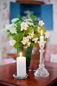 Pillar candle and standard candle in glass candle holders in front of green vase of jasmine on wooden table