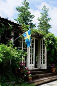 Rustic wooden house with Swedish flag and lattice doors