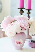 Pink vase of peonies in front of pink candles in candlesticks