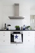 Black and white kitchen counter with stainless steel extractor hood and subway tiles on wall