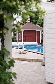 Swimming pool and Swedish, wooden summer house painted Falu red and white