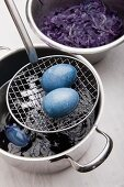 Eggs dyed using red cabbage on sieve spoon and pot of red cabbage
