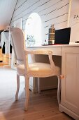 White, antique chair at desk in attic room with old, whitewashed wooden wall