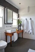 Rustic wooden table with countertop sink below windows in white tiled bathroom