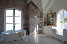 Free-standing bathtub in front of French windows and white fitted cupboards in bathroom with exposed brickwork