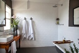 Rustic wooden table with countertop sink below window, open shower and bathtub in white-tiled bathroom