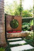 Stone flags amongst lawn in front of bench with red cushions and screen wall of rusty metal with circular aperture in tropical garden