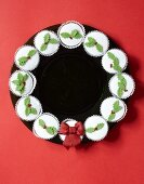 Circle of festively iced cupcakes on black plate