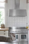 Stainless steel cooker below extractor hood against white-tiled wall