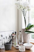Pestle and mortar, vintage bottles and white orchid on windowsill