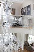 View from gallery with white wooden balustrade of Venetian-style, glass chandelier