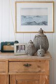 Set of three lanterns and photo on wooden sideboard against white, wood-clad wall