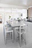 Pale grey bar stools at free-standing counter in open-plan kitchen with white wooden floor