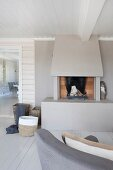 Open fireplace with surround painted pale grey in wood-clad interior