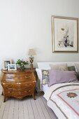 Rococo-style chest of drawers next to bed on pale wooden floor in rustic bedroom