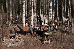 Campfire, picnic, table, tent and bicycle in autumn woods; man relaxing with back against tree trunk