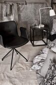 Designer chair next to cushions on floor, white bedside lamp on cube-shaped side table and grey patterned wallpaper