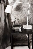 White, retro table lamp and jug of water on black side table against grey-patterned wallpaper