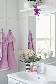 Vase of flowers on sink, potted orchid above mirror and lilac towels on hooks in white bathroom