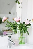Bicolour peonies in glass vase on sink reflected in mirror