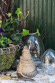 Wooden cone of twine, scissors and glass eggs next to Easter arrangement in wire basket