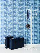 Blue wallpaper, white coat stand and blue leather suitcases