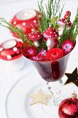 Christmas arrangement of roses, geranium flowers & ornamental fly agaric mushrooms in glass goblet