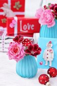 Christmas decorations in blue & red with flowers in vases, baubles & gifts
