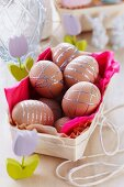 Brown eggs decorated with silver stickers in chip wood box