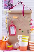 Packpapierrolle als Notizwand aufgehängt an Regalwand & dekoriert mit Büroklammern, Klebezetteln, Anhängern & Stiften