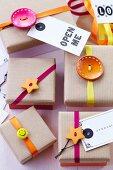 Geschenkkartons mit Deckeln aus Packpapier verziert mit Knöpfen, Bändern & Anhängern