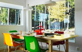 Colourful shell chairs around wooden table in corner; view of woodland through panoramic window