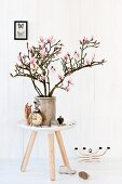 Branches of magnolia in stoneware pot on Tablo side table