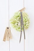 Wreath of green carnations tied with black and white striped ribbon