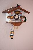 Cuckoo clock with small figurine on swing suspended beneath on pink-painted wall