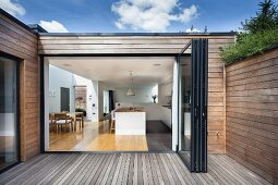 Wooden terrace of contemporary house with wood-clad facade; view through open folding door into kitchen