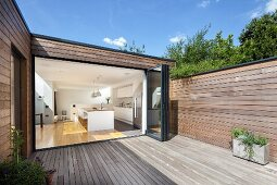 Wooden deck of contemporary house with wood-clad facade; view into kitchen through open folding door
