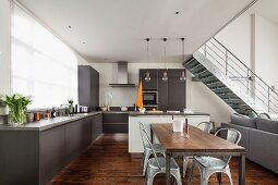 Open-plan interior in shades of grey with dining area and metal staircase in background