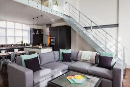 Grey sofa and coffee table in open-plan interior; fitted kitchen below gallery in background and metal staircase