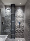 Designer bathroom - shower area with glass screen, tall metal shelves against tiled wall with 3D structured surface