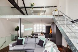 Grey corner sofa and gallery with metal staircase in open-plan, loft-style interior