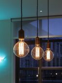 Row of pendant lamps with large, decorative light bulbs in front of window at twilight