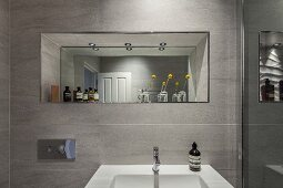 Washbasin on tiled wall below mirror in niche