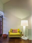 Yellow designer armchair and white plastic standard lamp in corner
