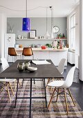 Blue Murano glass lampshade above black table and Eames Plastic Chairs in front of kitchen counter