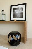 Black and white picture on simple console table and cubic plastic stool