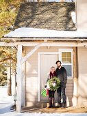 Young couple holding wreath standing in front of house