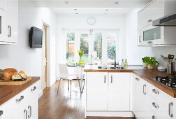 Open-plan fitted kitchen with white fronts and wooden work surfaces; dining area with French windows leading to garden