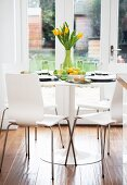White wooden chairs at a round table laid with a bunch of yellow flowers with garden doors in the background